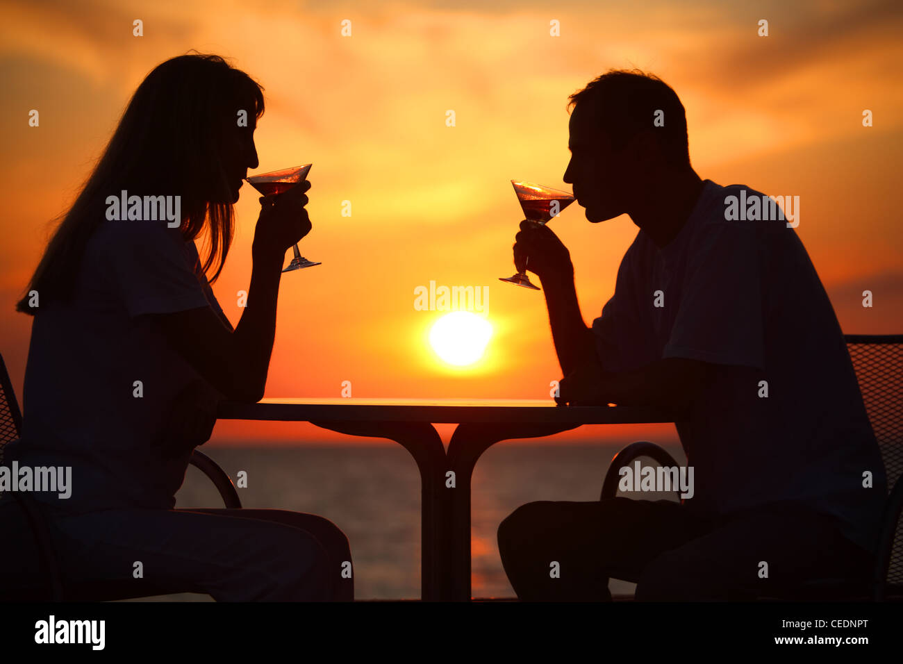 Female and man's silhouettes on sunset  drink from glasses - Stock Image
