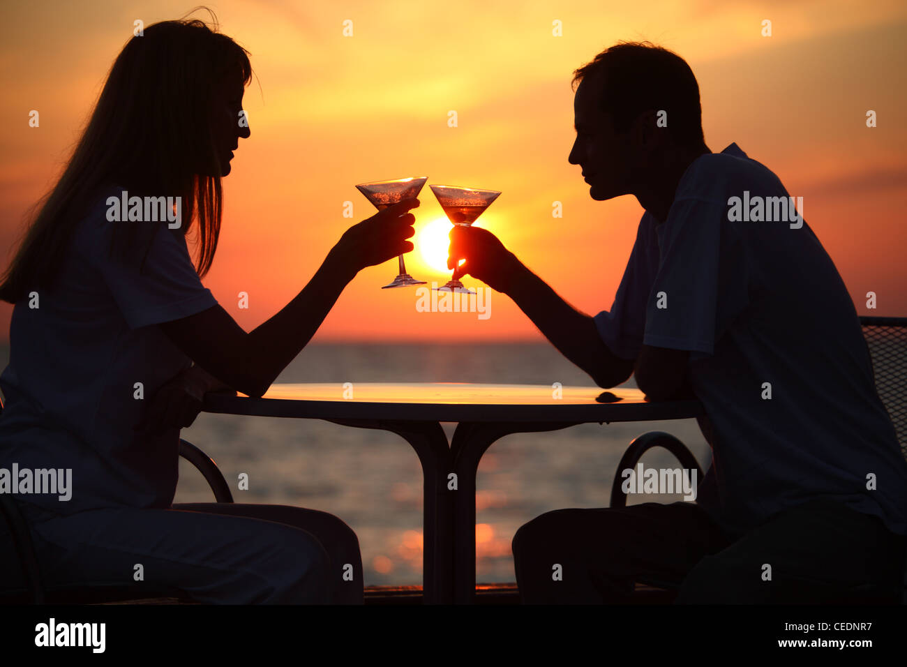 man and woman clink glasses on sunset outside - Stock Image