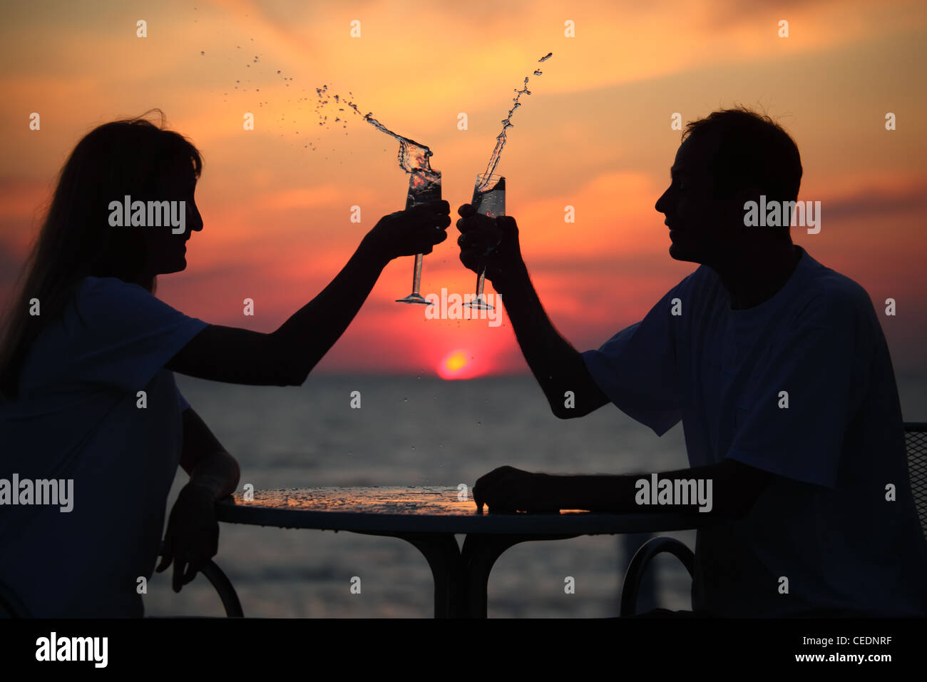 silhouettes of man and woman splash out drink from glass on sea sunset. focus on man - Stock Image