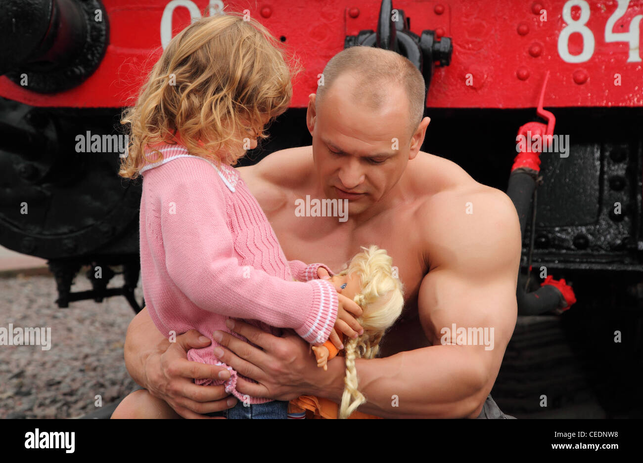 strong shirtless man sits on railroad with little girl Stock Photo