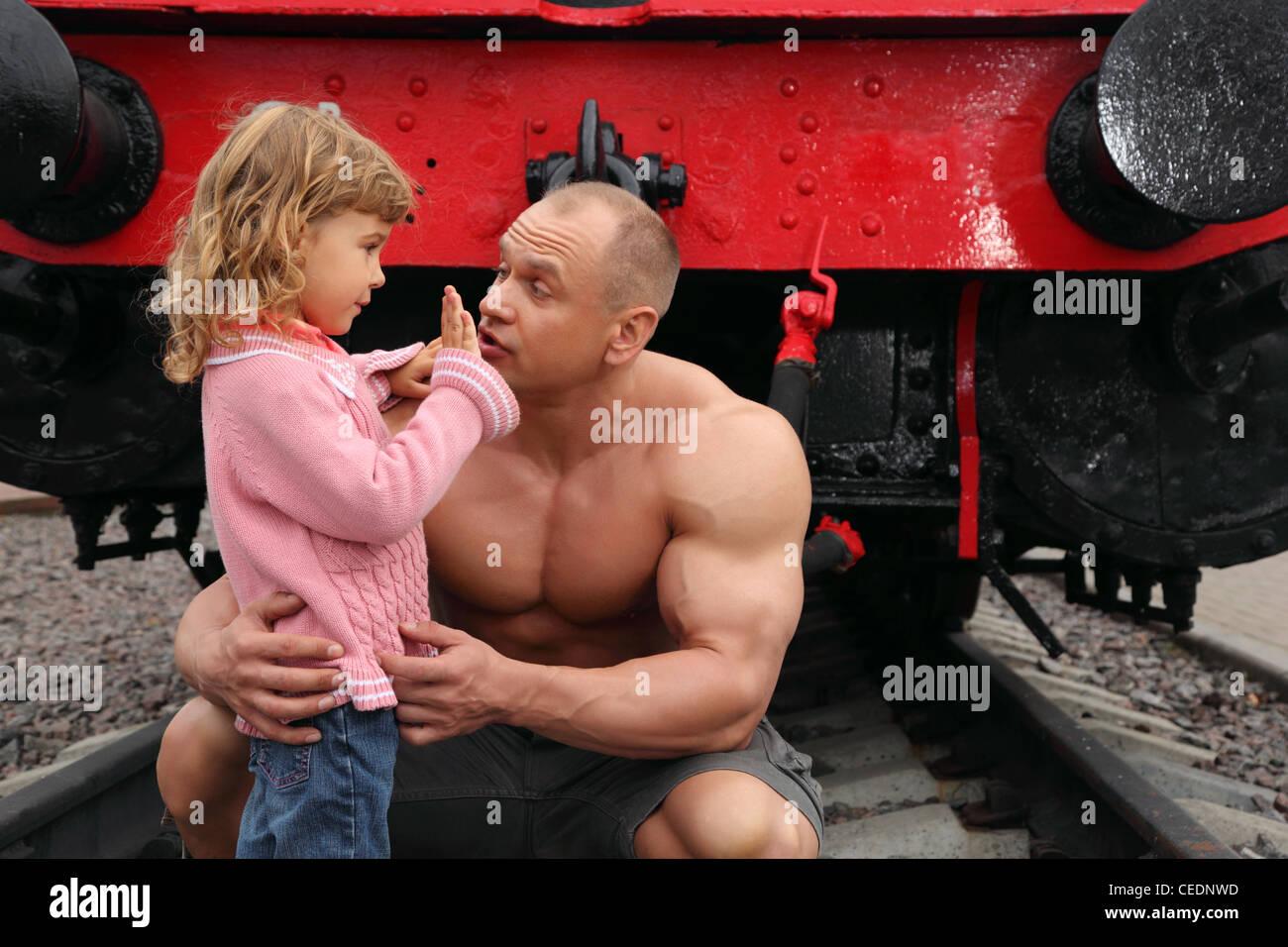 Strong Shirtless Man Saving Little Girl On Railroad Stock