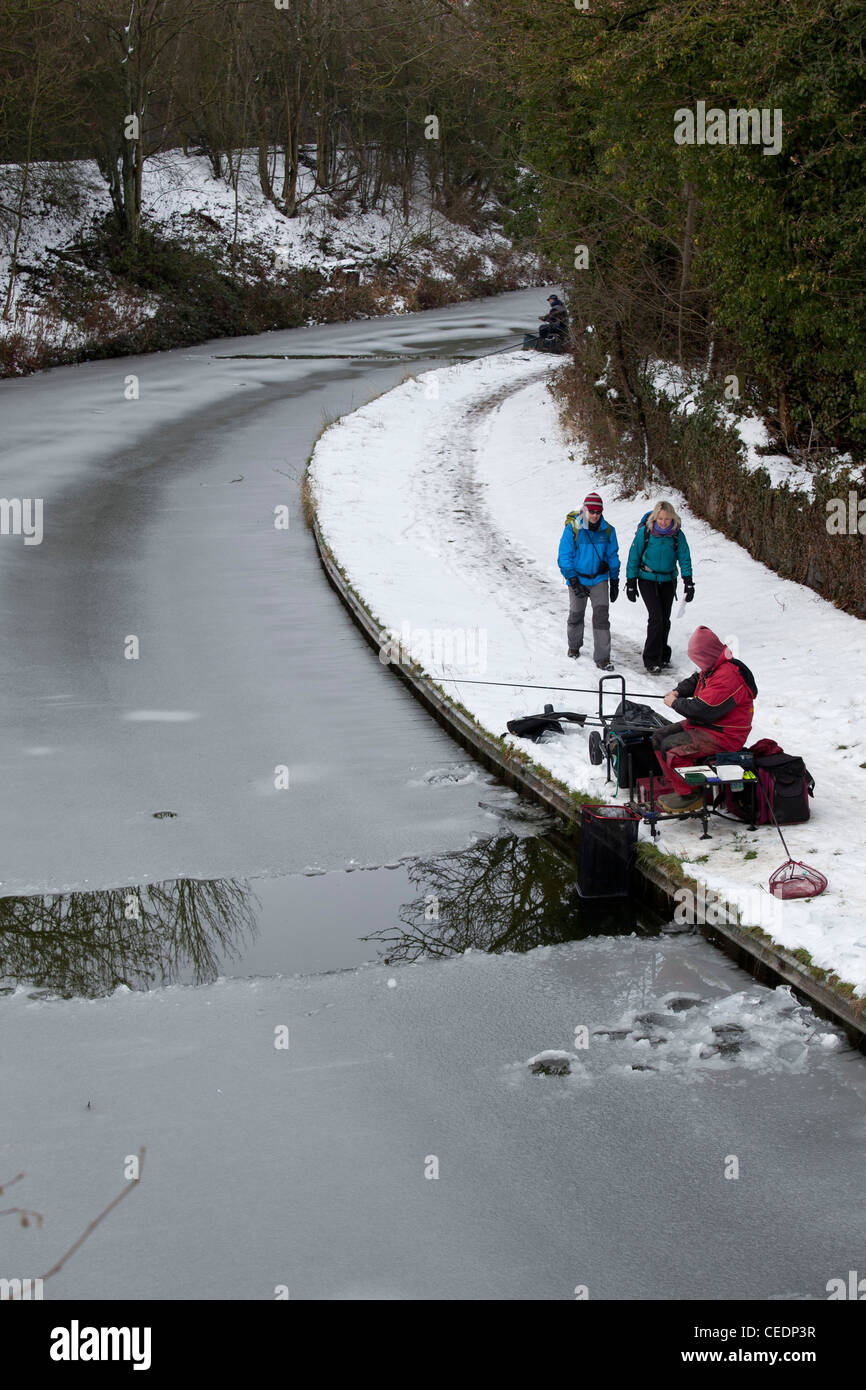 Fishermen fishing in the Coventry canal, Nuneaton, Warwickshire, after breaking the ice on the frozen canal. - Stock Image
