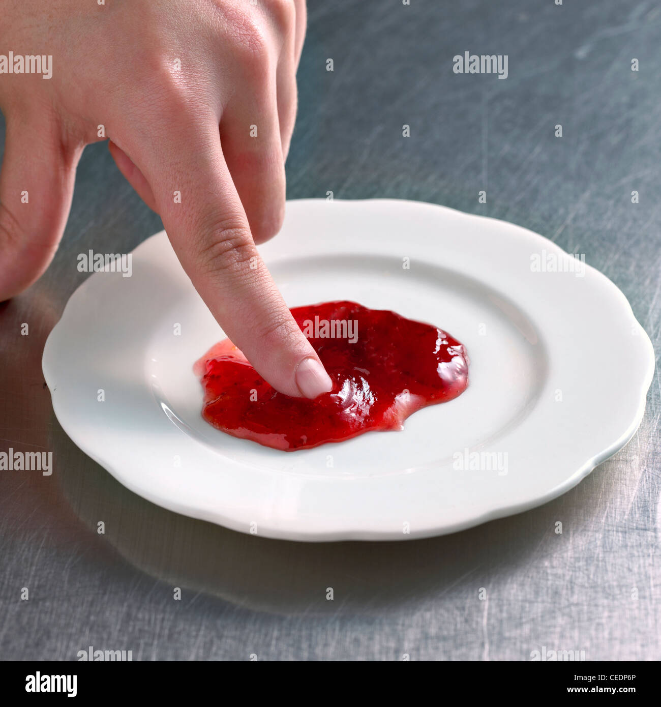 Hand doing wrinkle test of jam, close-up - Stock Image