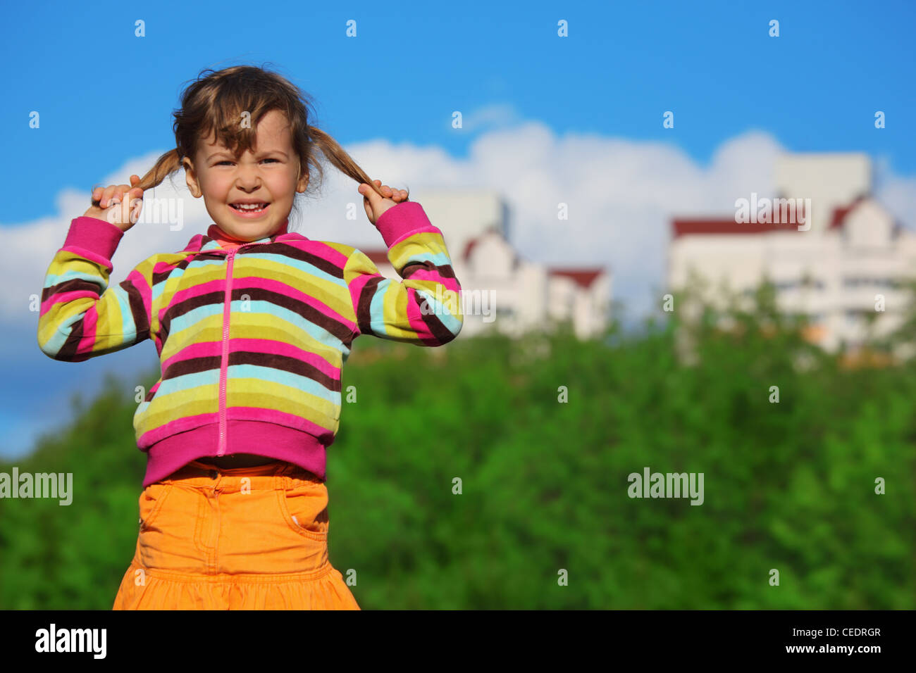 little girl holding plaits in front of trees and buildings - Stock Image