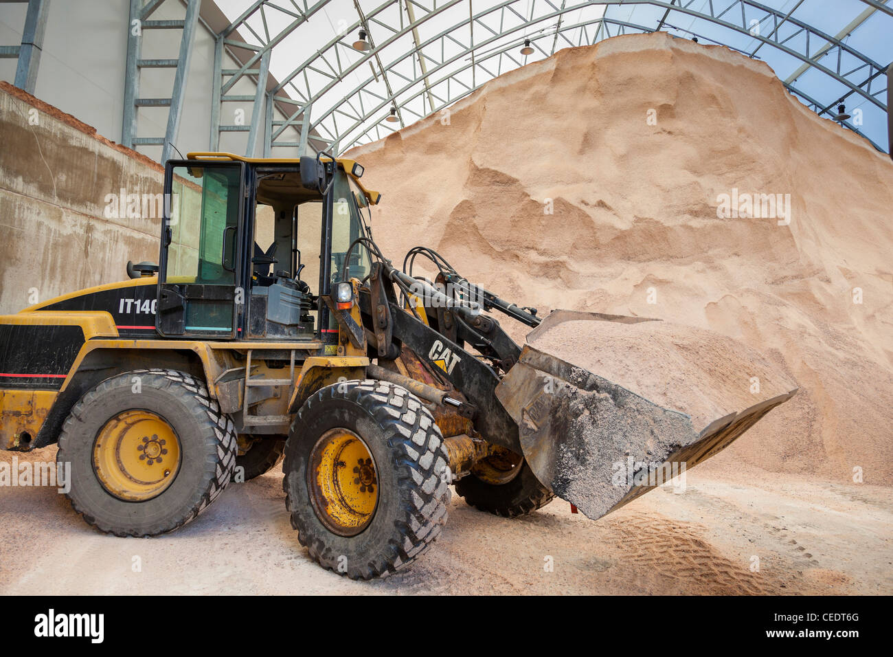 Road grit store with mechanical shovel or digger. - Stock Image