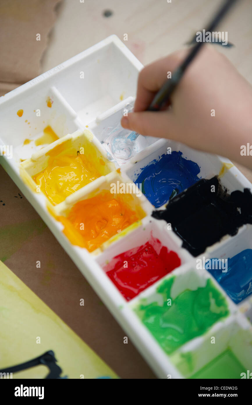 Child holding paintbrush in white paint in palette, close-up - Stock Image