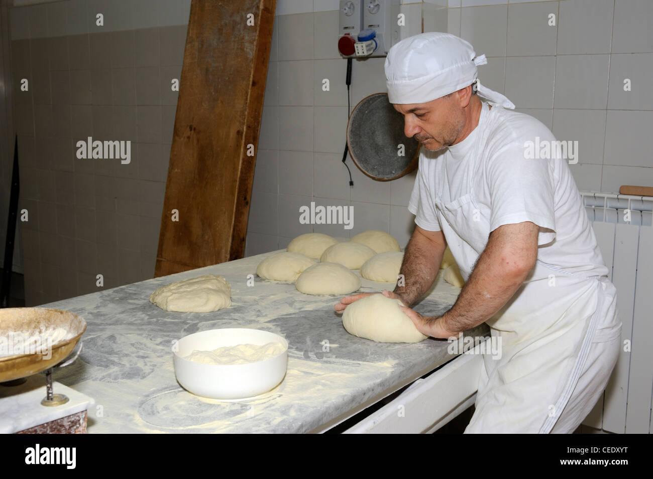 italy, basilicata, bakery, baker kneading bread Stock Photo
