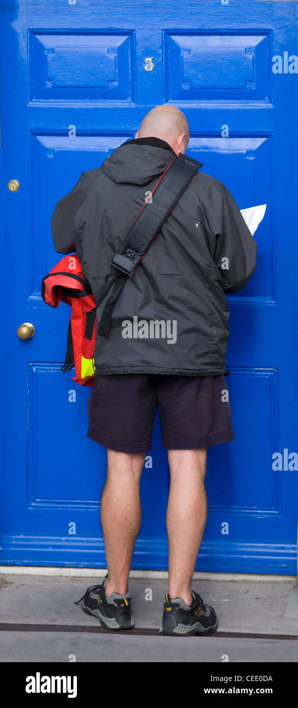 A UK Royal Mail postman delivering to a house with a blue door - Stock Image