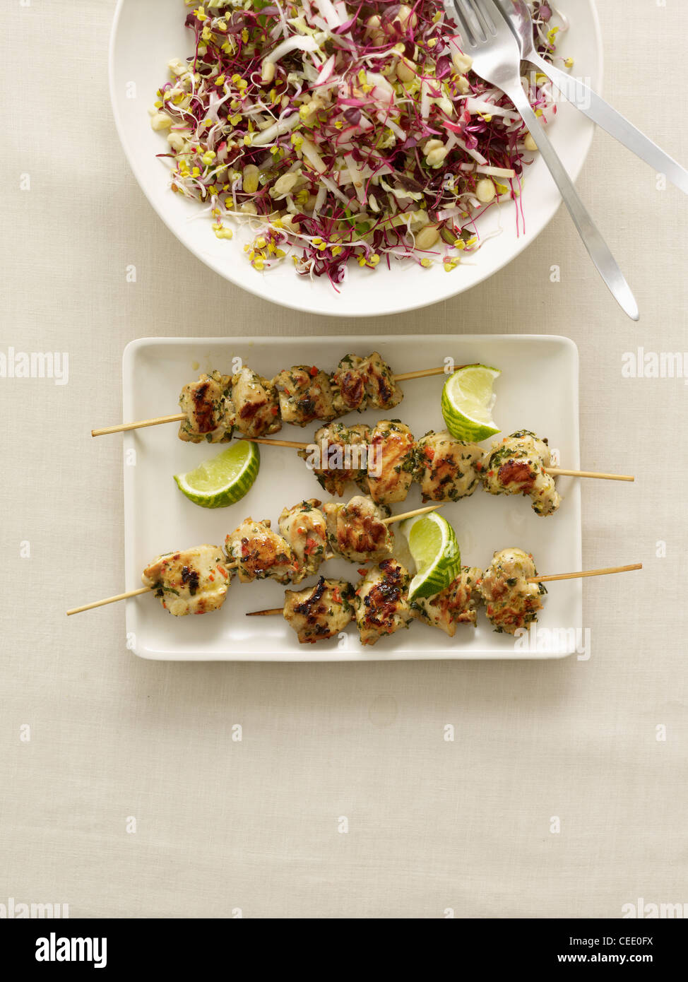 chicken skewers satay sticks limes overhead view - Stock Image