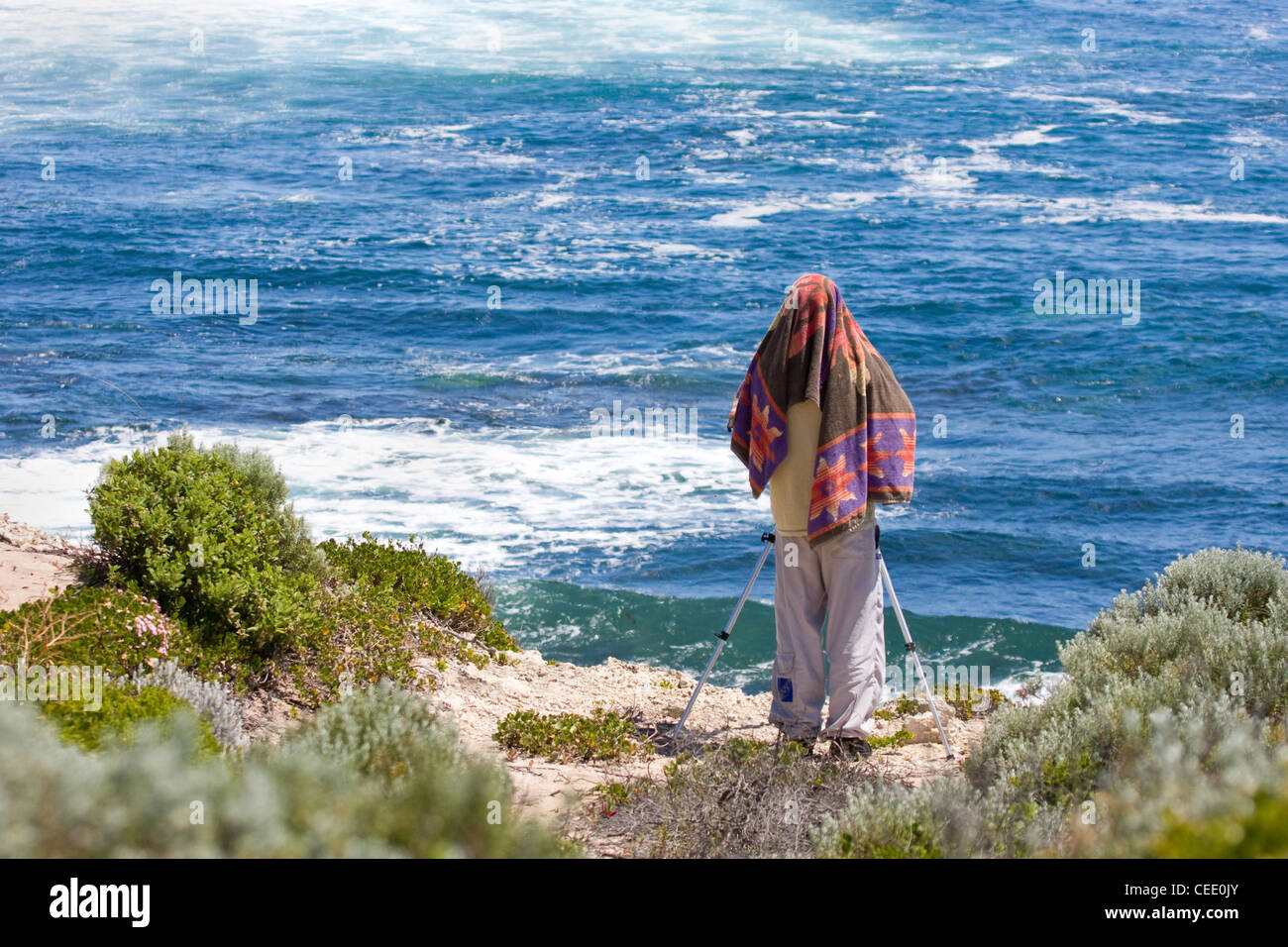 A  photographer shields himself from the hot sun using a beach towel in Western Australia near Margaret River - Stock Image