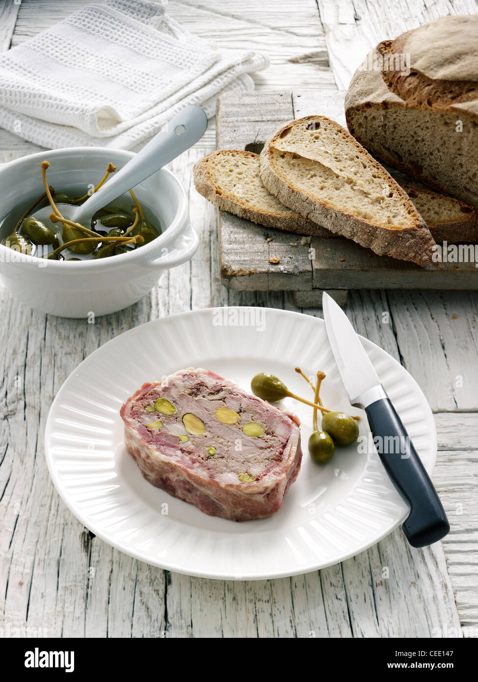 Duck pate capers crust bread white plate - Stock Image