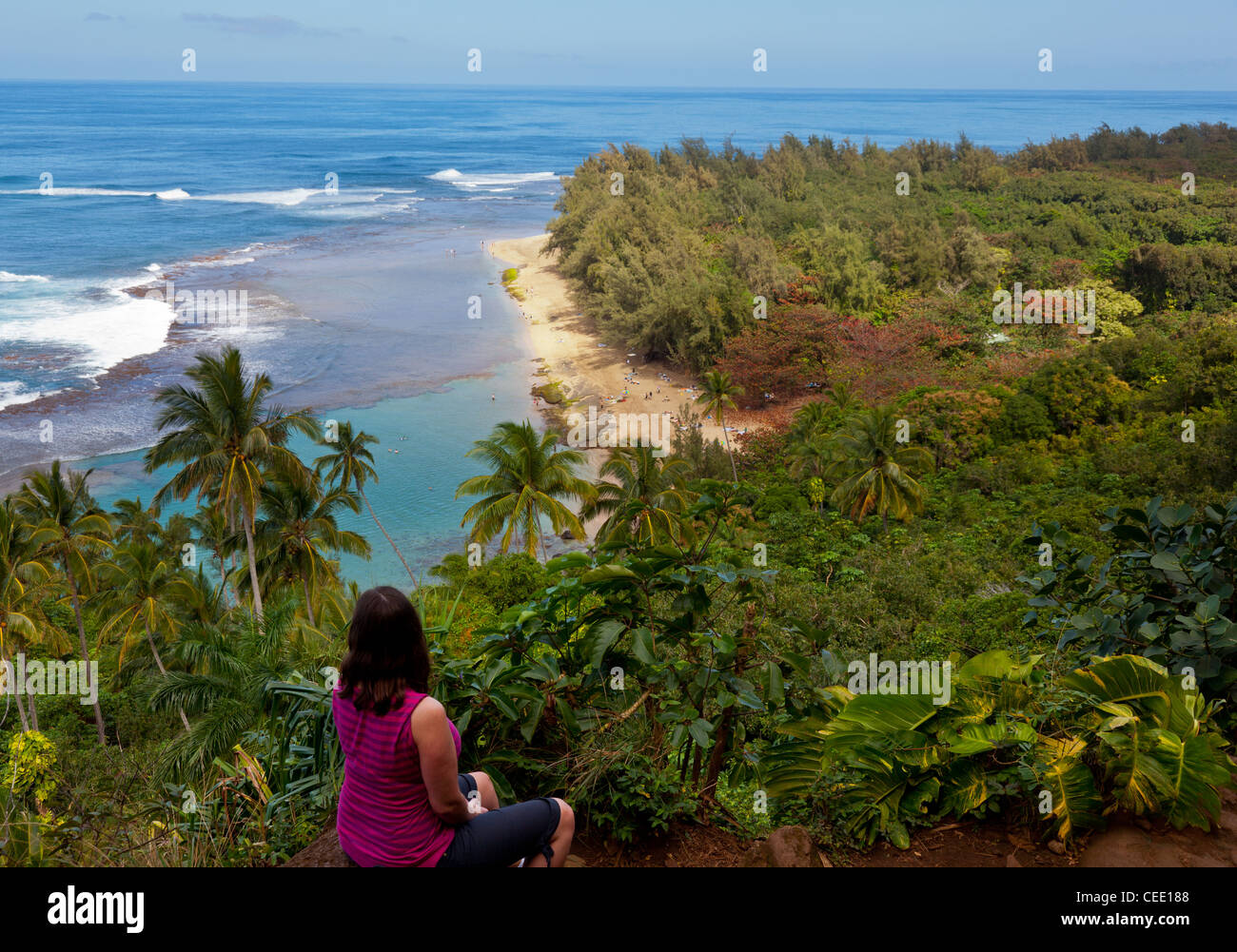 Female hiker overlooking Kee beach from Kalalau trail on Na Pali coast of Kauai, Hawaii - Stock Image