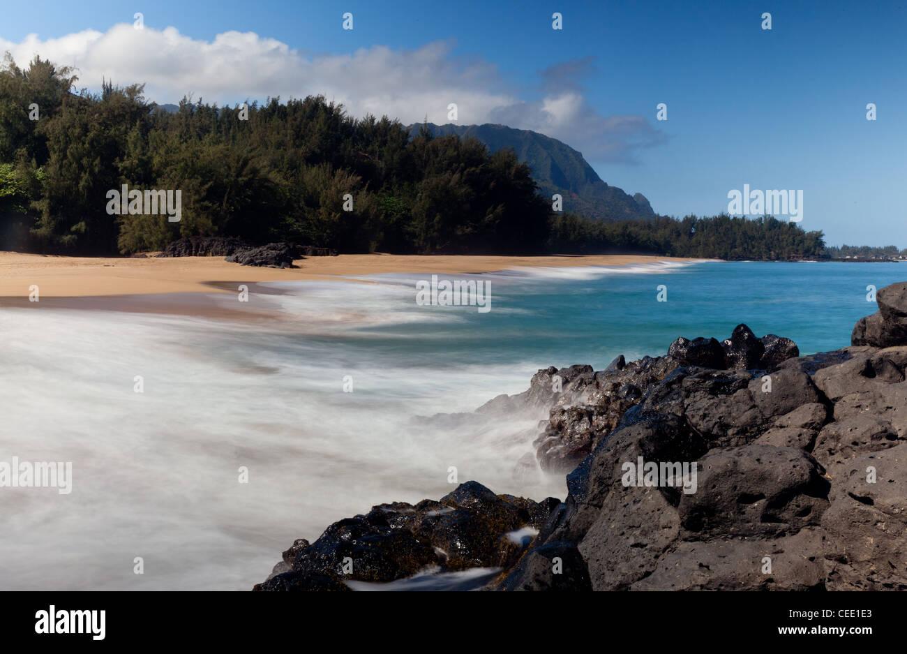 Waves crash onto Lumahai beach on Kauai Hawaii with Na Pali Coast - Stock Image