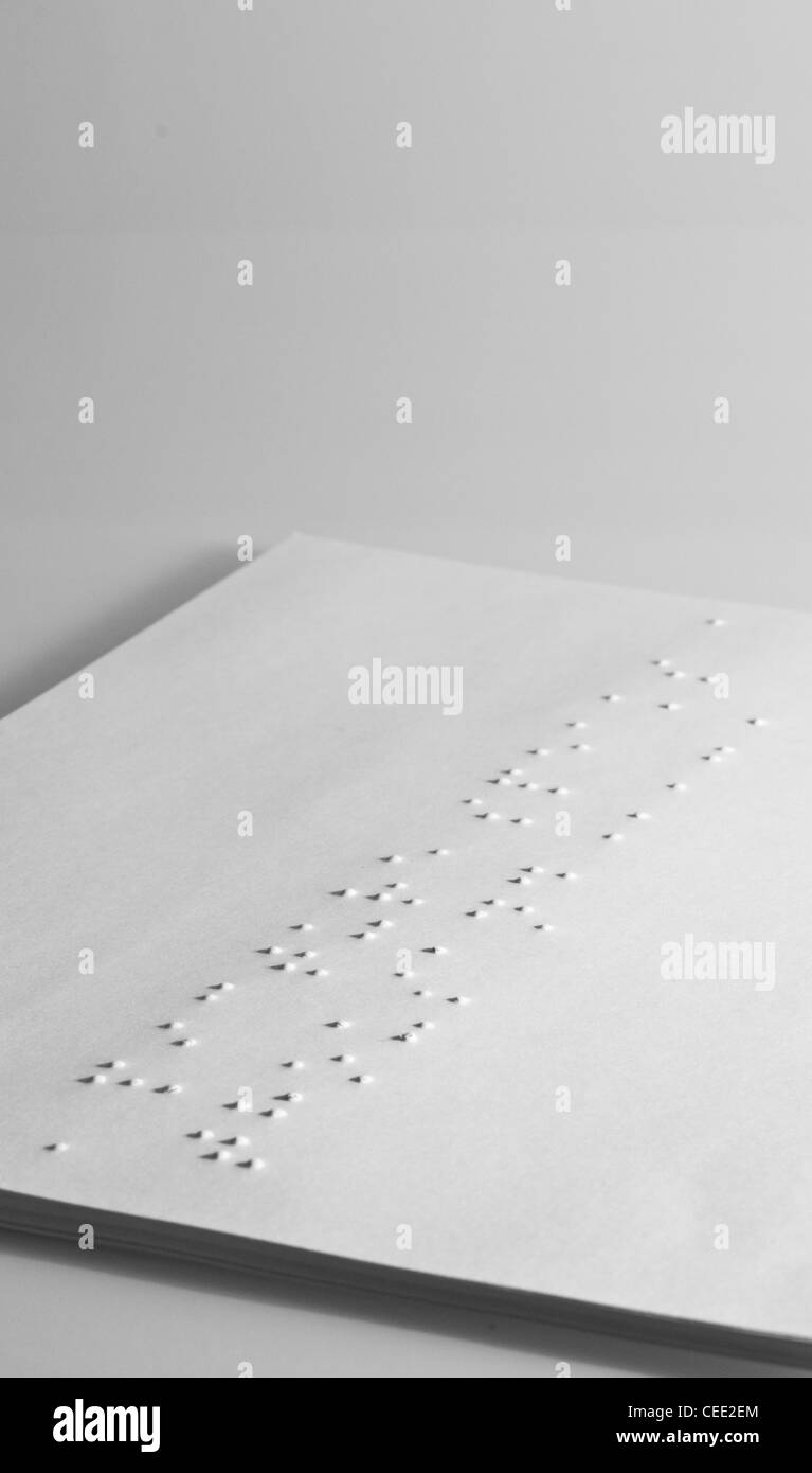 stack of white paper with braille on top sheet - Stock Image