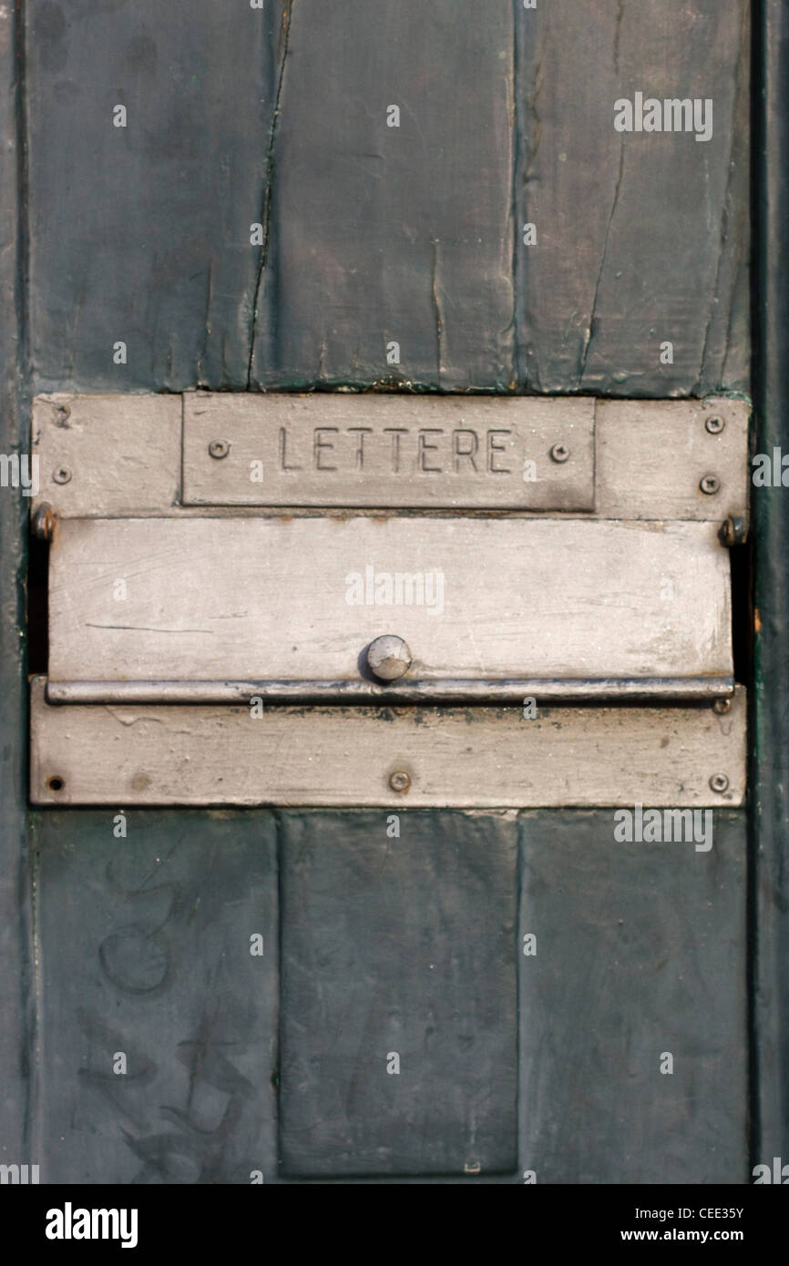 A Golden colored letterbox on a wooden door - Stock Image