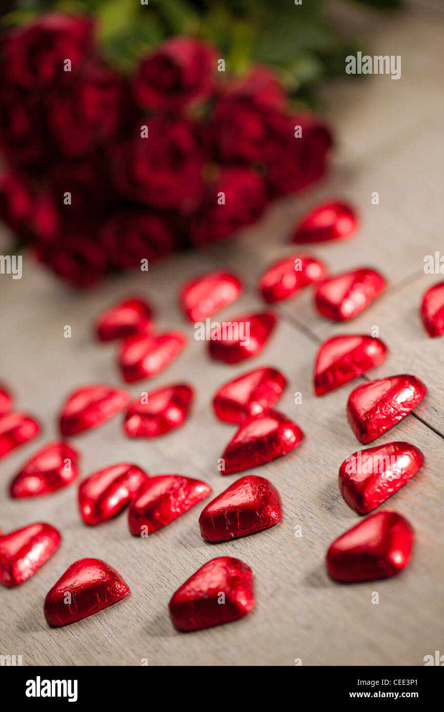 Chocolate shaped heart sweets wrapped in red foil and red roses - Stock Image