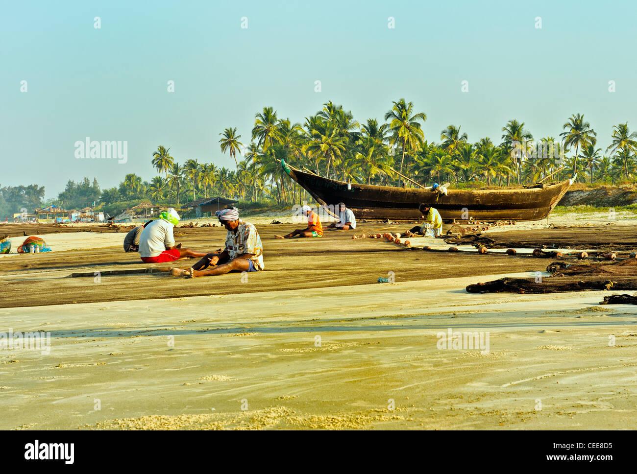 Fishermen repairing fishing nets on Varca Beach, Goa, India - Stock Image