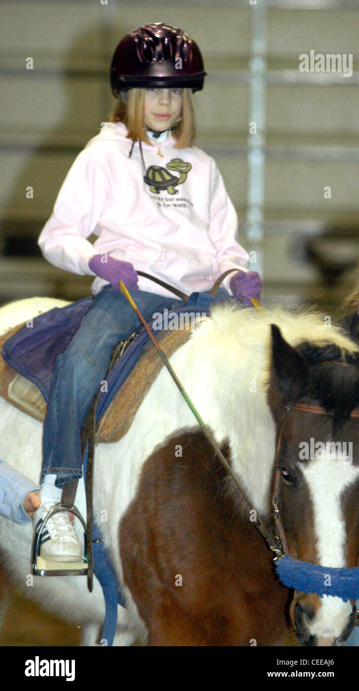Erin Pelton, age 13, rides a horse during a weekly therapy session at Pikes Peak Therapeutic Riding Center in Colorado - Stock Image