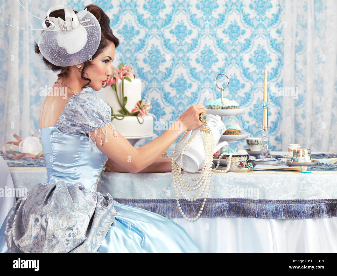 Beautiful asian lady in a luxurious blue dress sitting at a table and pouring tea ina cup. Tea party hostess. - Stock Image