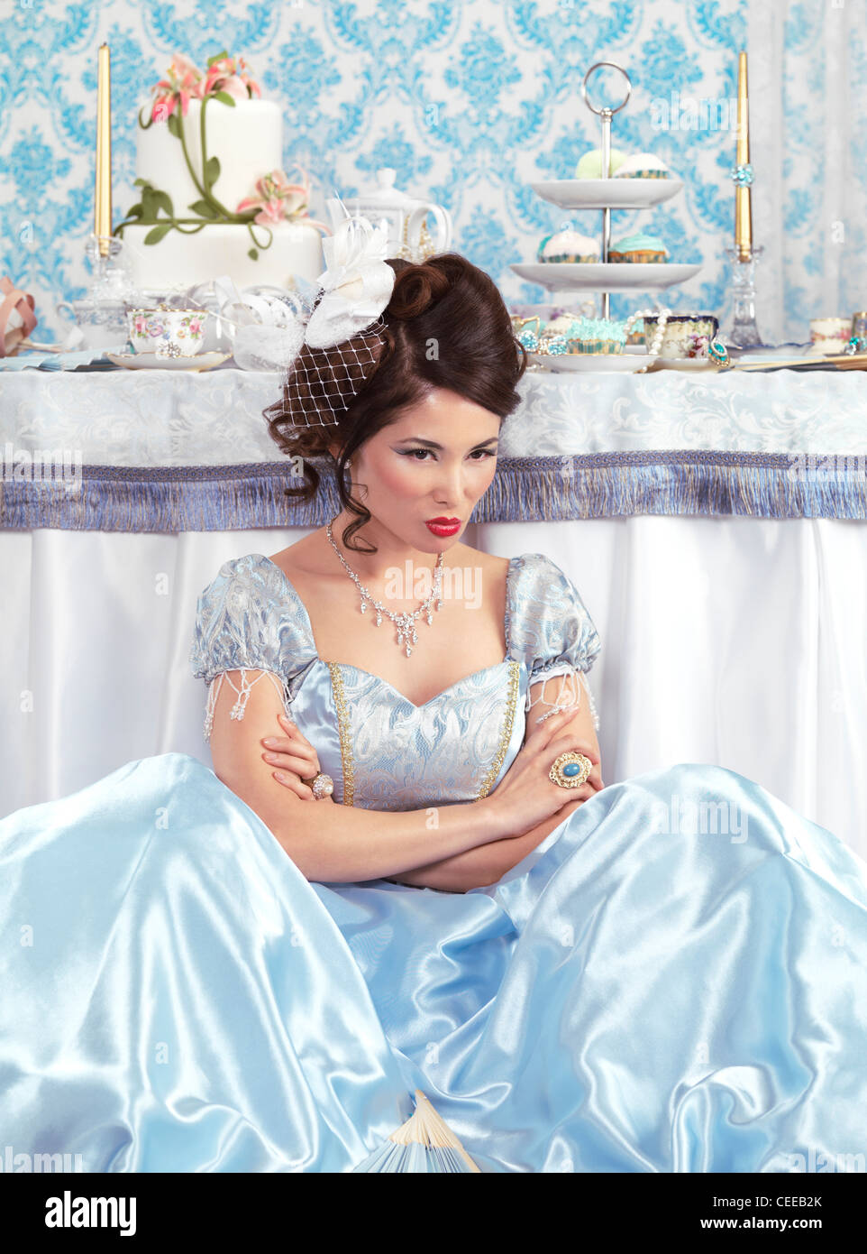 Beautiful asian lady with a sulky pout sitting on the floor beside a party table Stock Photo