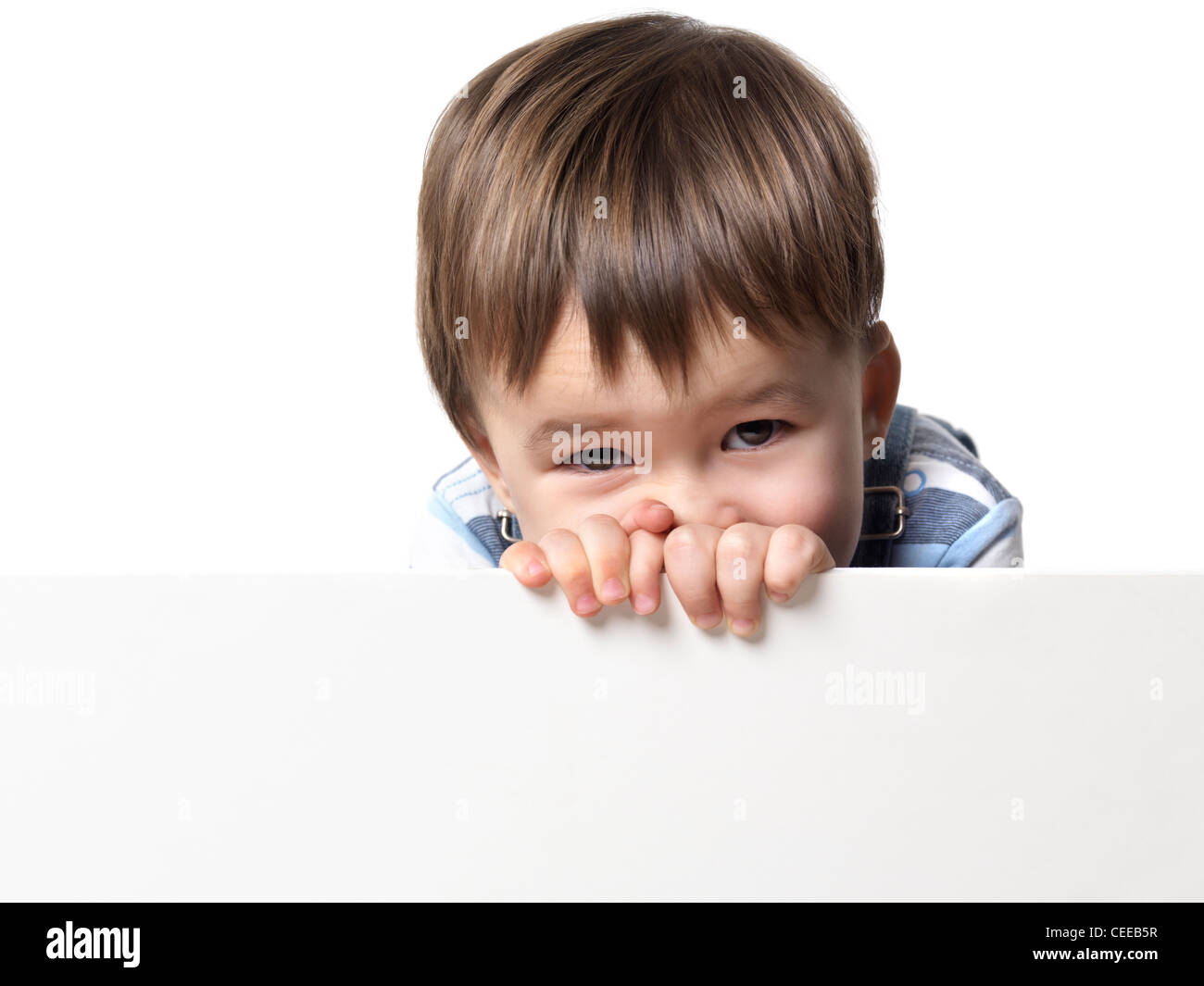 Two year old boy behind a white sign isolated on white background with copyspace - Stock Image
