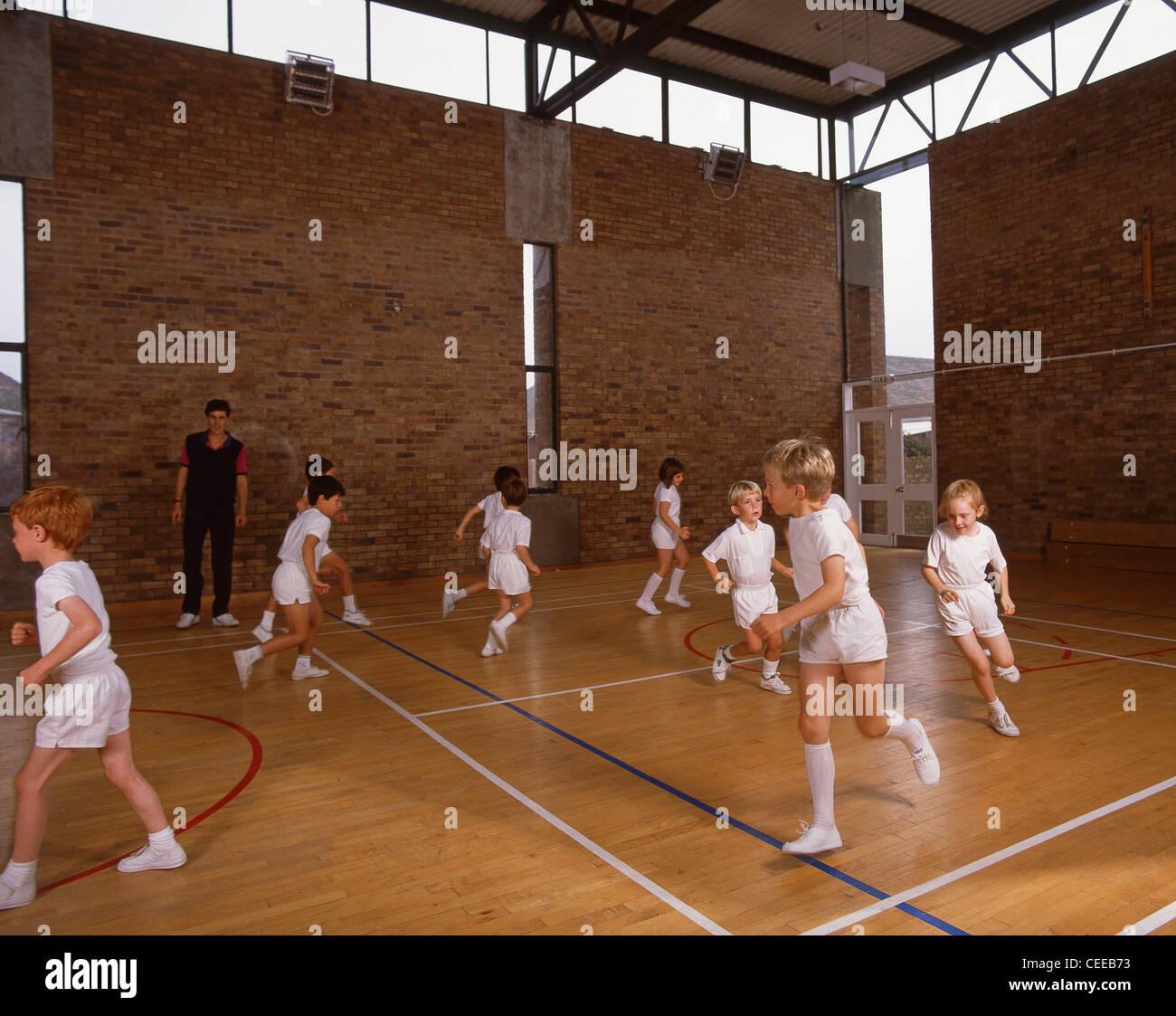 School children excercising in gym, Surrey, England, United Kingdom - Stock Image