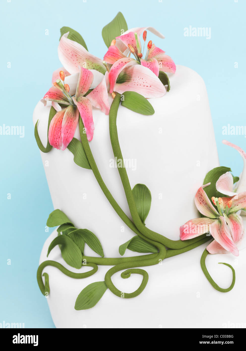 Fancy cake decorated with lilies isolated on blue background - Stock Image