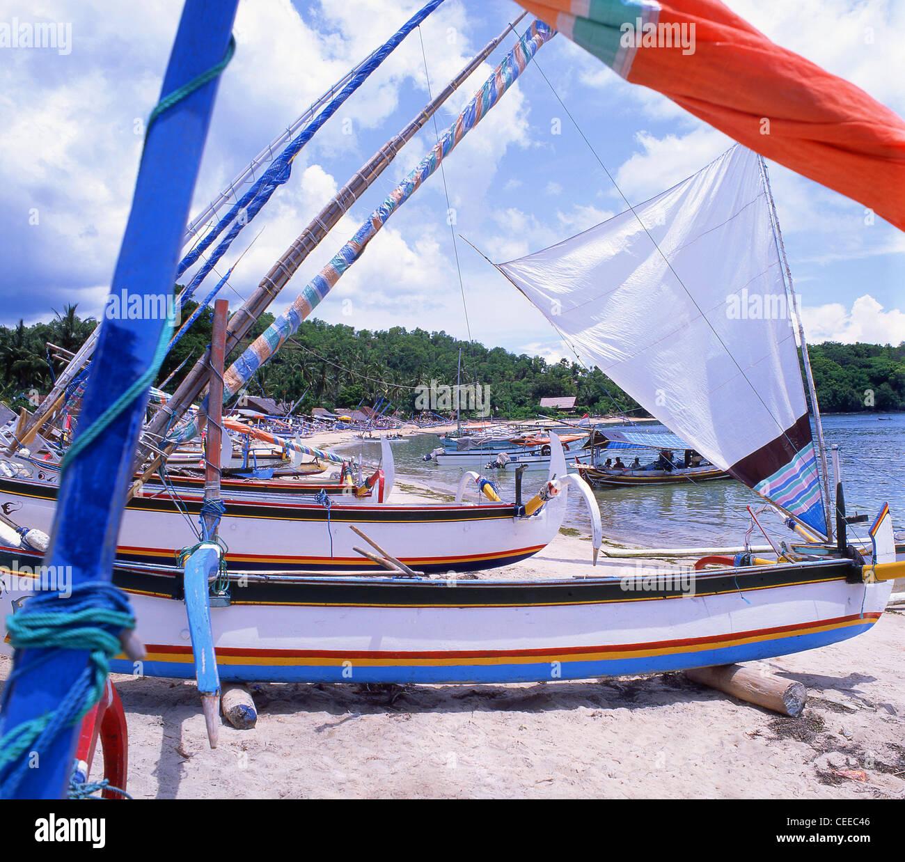 Jukung outrigger sailboats on beach, Padangbai, Bali, Bali Province, Lesser Sunda Islands, Indonesia - Stock Image