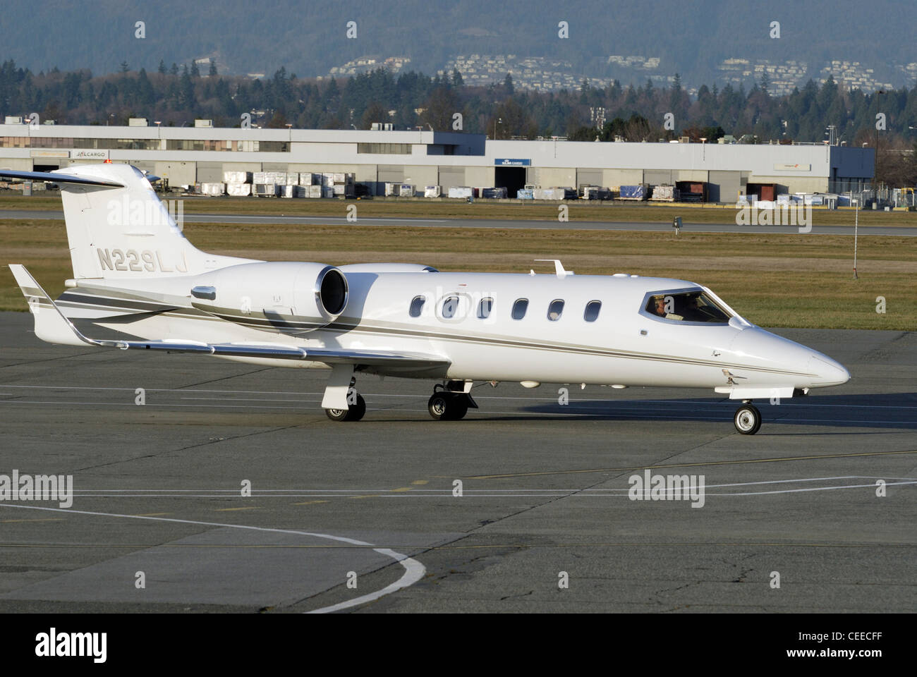 Learjet 31A (twin-jet) taxiing at Vancouver International Airport. - Stock Image