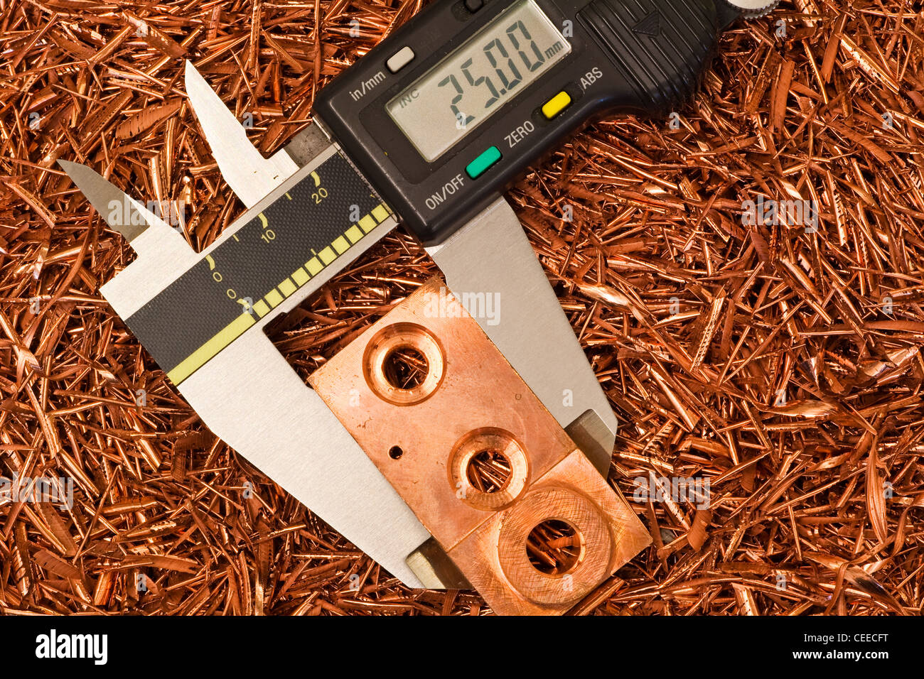 An electronic vernier caliper used to measure a copper component - Stock Image