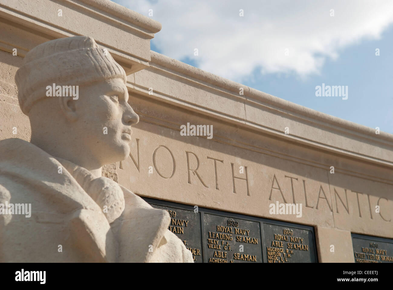 Stone statue representing a sailor in World War Two with North Atlantic memorial panels behind, Naval War Memorial, - Stock Image