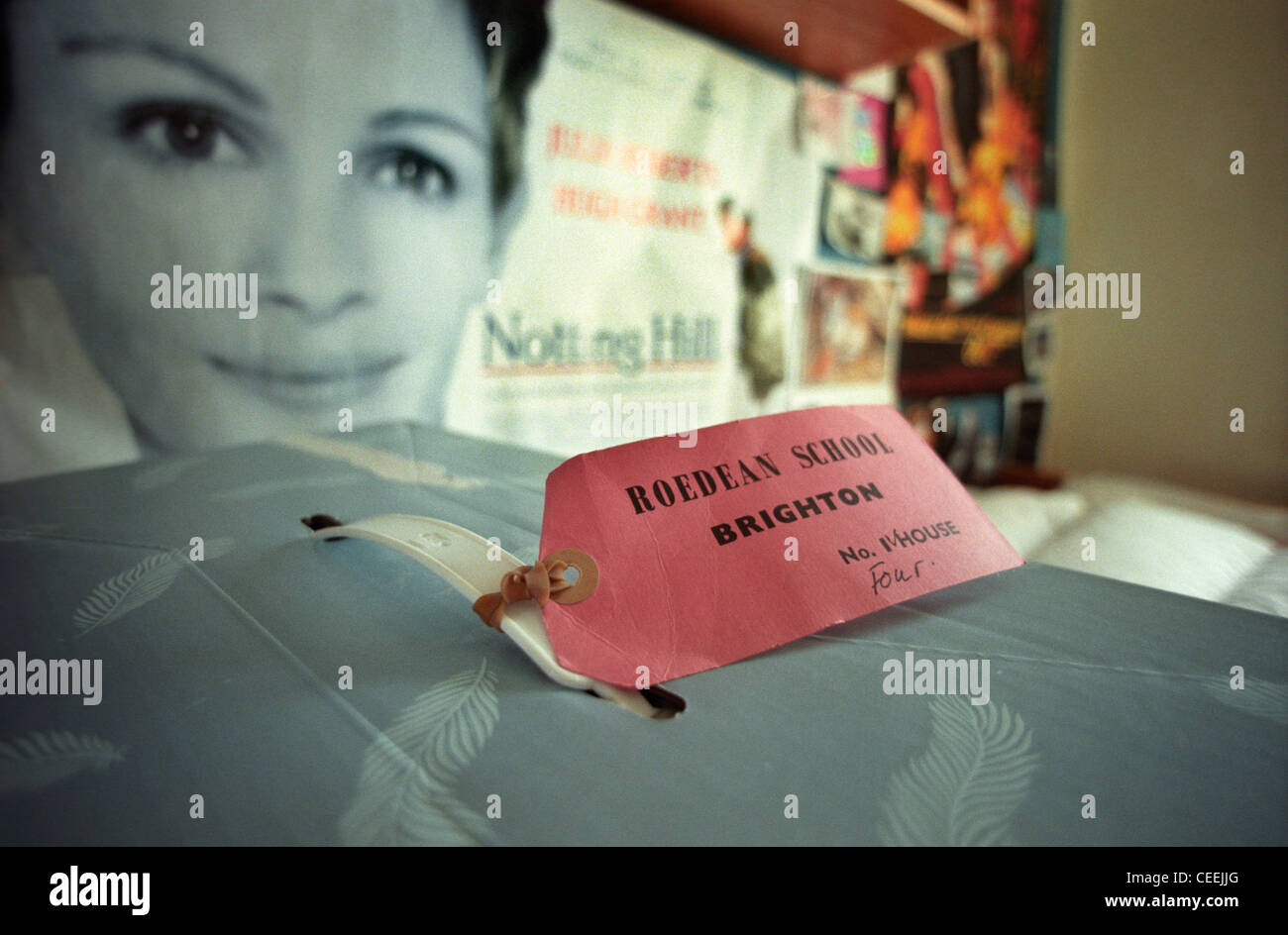 A Roedean schoolgirl's case with luggage label on the bed in front of a Julia Roberts 'Notting Hill' - Stock Image