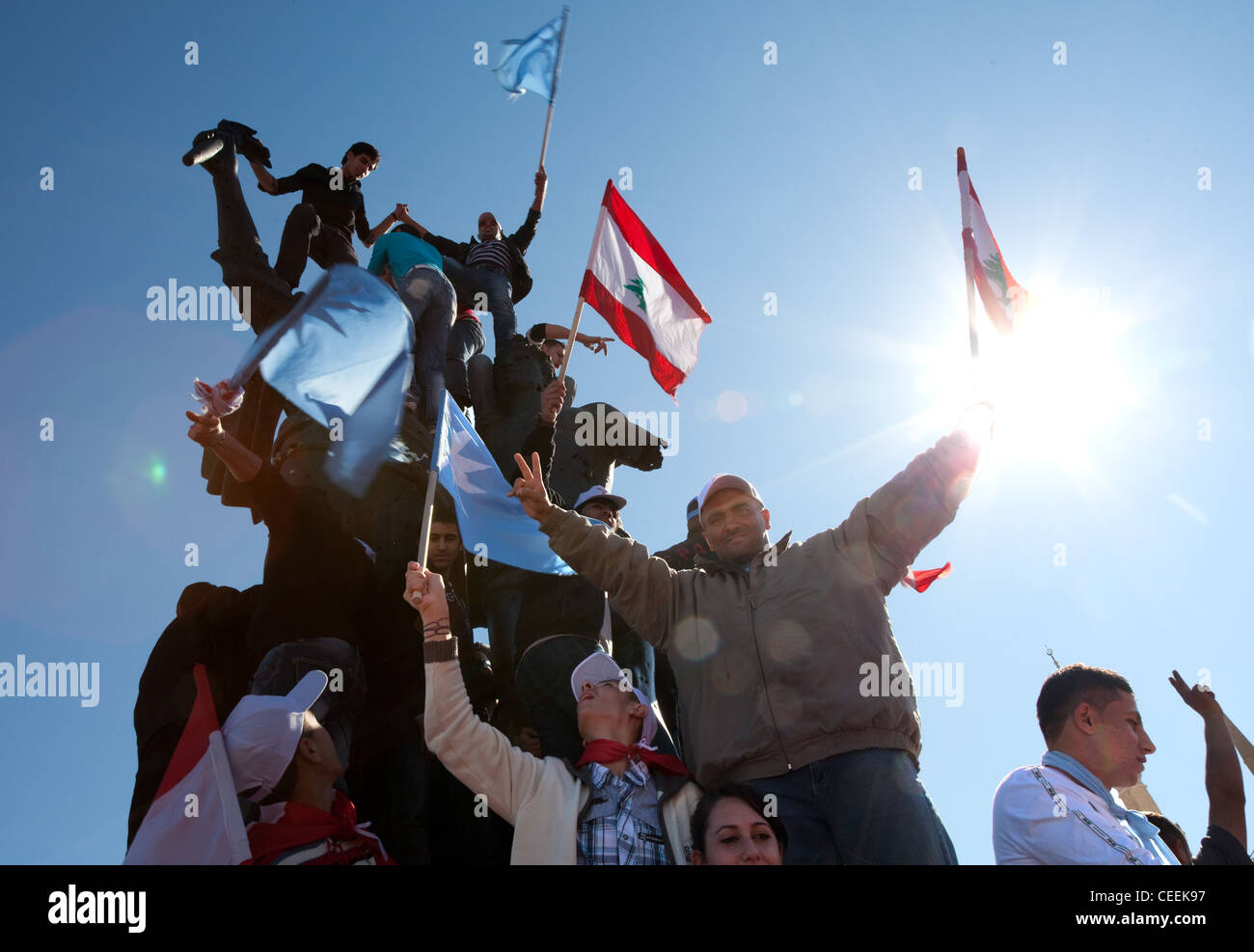 Political supporters with flags clamber over Martyrs Square monument in Beirut, Lebanon during Arab Spring of 2011. Stock Photo