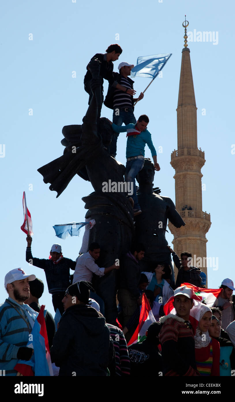 Political supporters with flags clamber over Martyrs Square monument in Beirut, Lebanon. Minaret in background Stock Photo
