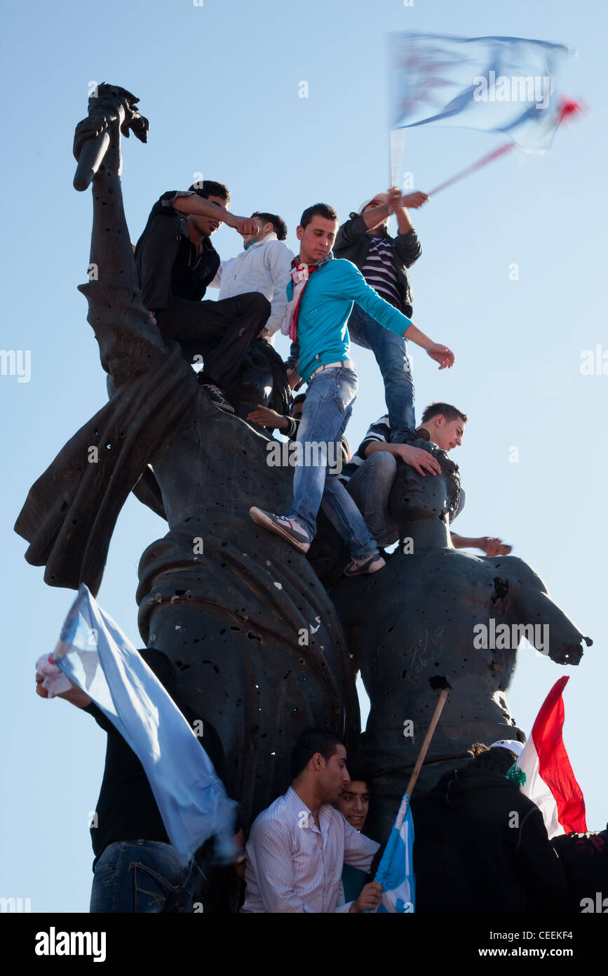 Political supporters with flags clamber over Martyrs Square monument in Beirut, Lebanon. Stock Photo