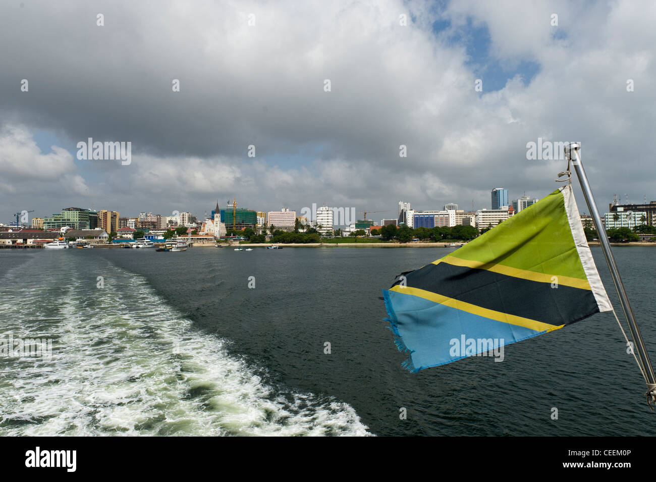 Harbor front of Dar es Salaam and Tanzanian flag on a ferry to Zanzibar Tanzania - Stock Image