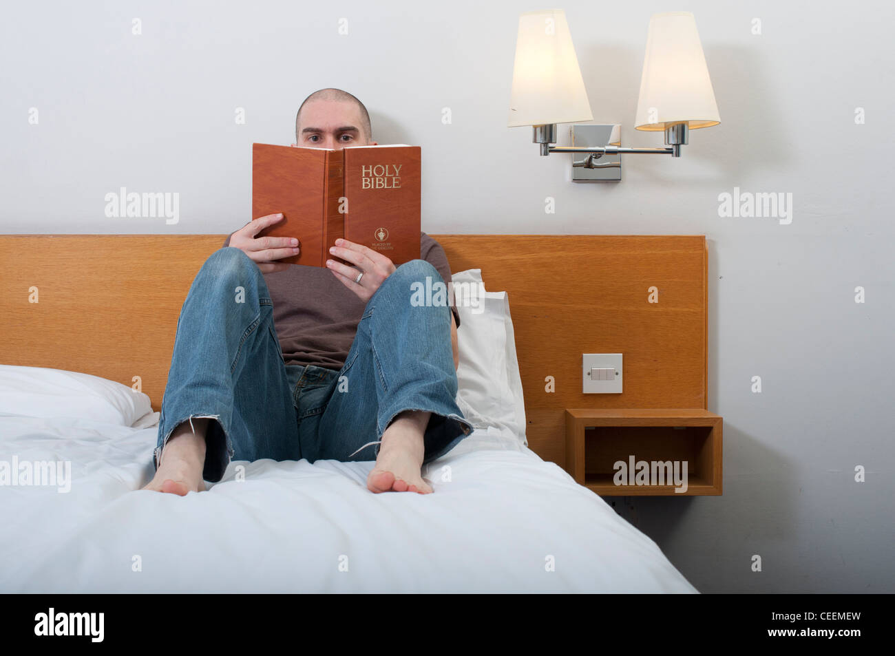 Man, 30-40 years, reading Holy Bible in a hotel room. - Stock Image
