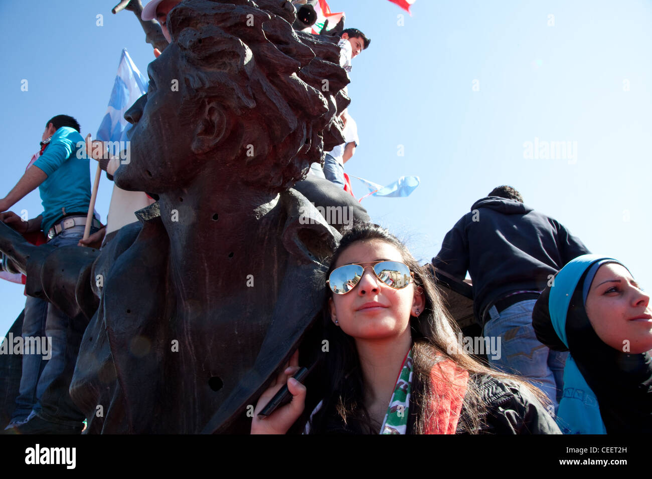Young woman with sunglasses and uncovered hair stands at Martyrs Square statue during mass political rally in Beirut, Stock Photo