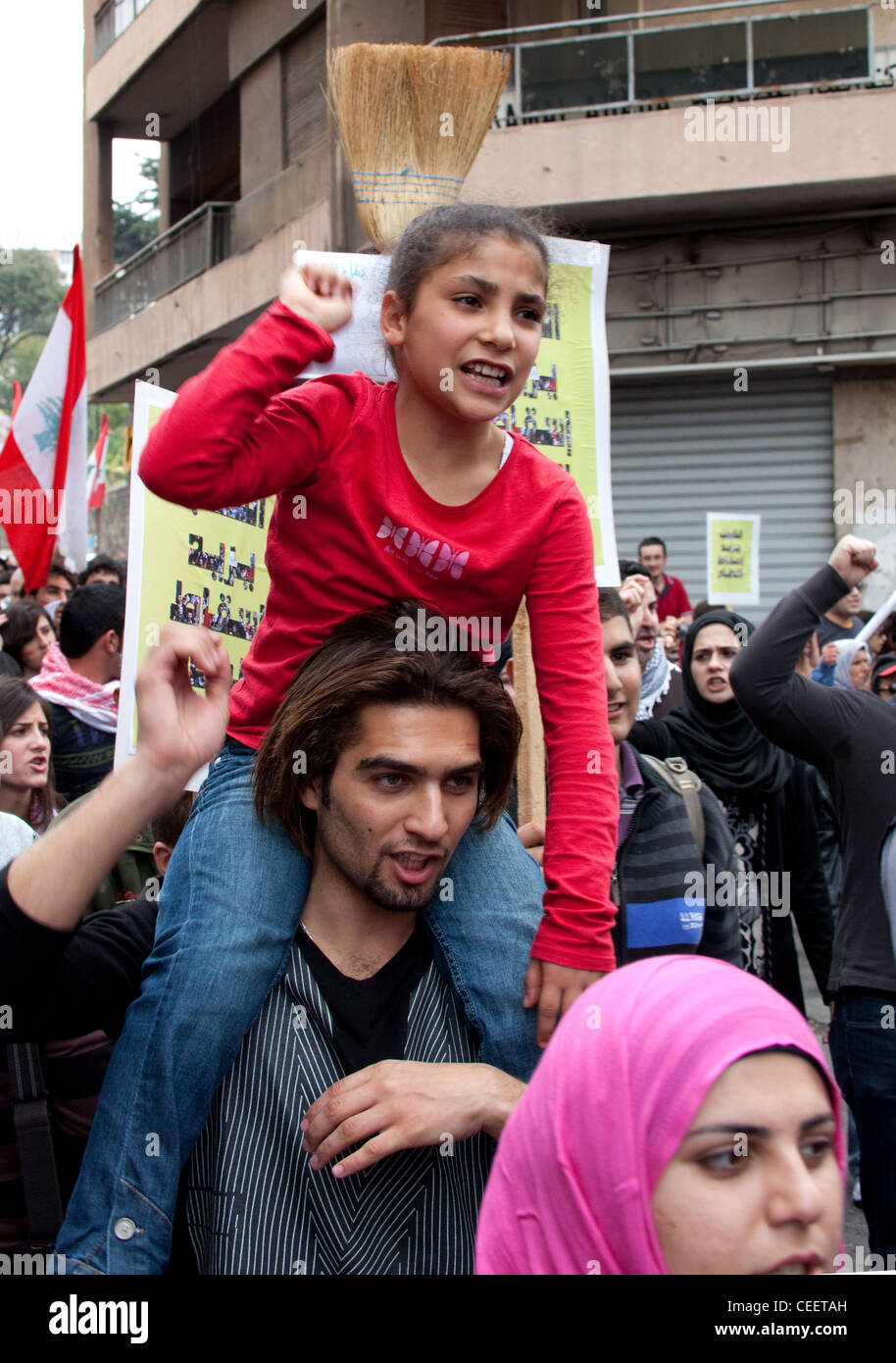 Young girl chants political slogans as she is carried on shoulders of young man at political demonstration in Beirut, Stock Photo