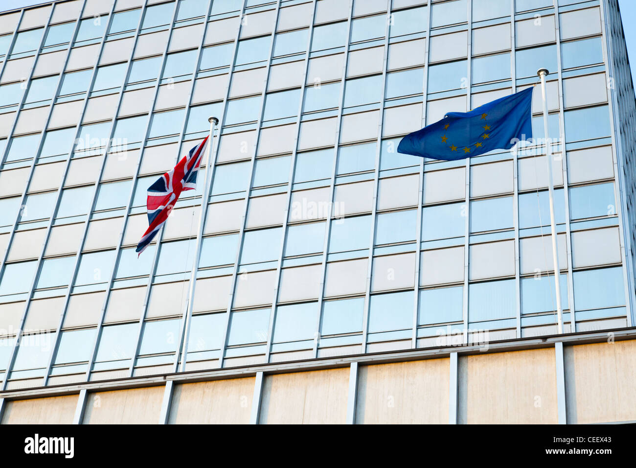 UK flag and EU flag flying together. Union Jack and the European Union flags flying outside offices in Nottingham, - Stock Image