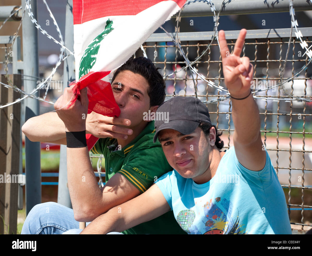 Lebanese teenagers kiss flag and make victory sign at political rally in Martyrs Square, Beirut. Behind razor wire Stock Photo