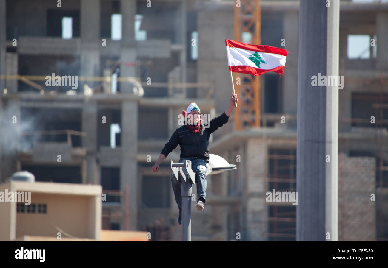 Young Lebanese man on top of streetlamp waves flag high as mass political rally in Martyrs Square, Beirut, Lebanon Stock Photo