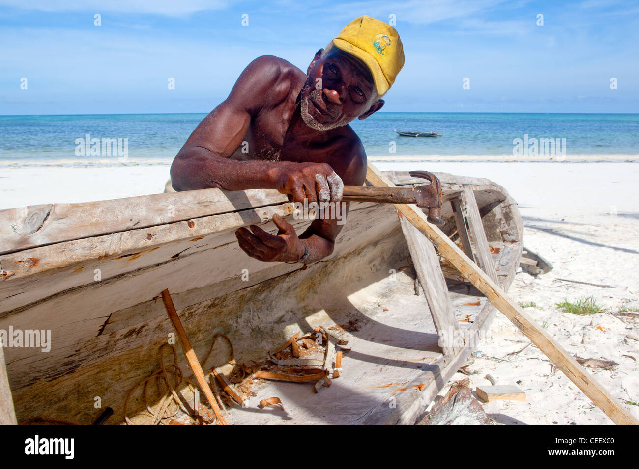 Old Zanzibari man repairing a wooden dhow on the beach at Bwejuu, Zanzibar Island, Tanzania - Stock Image