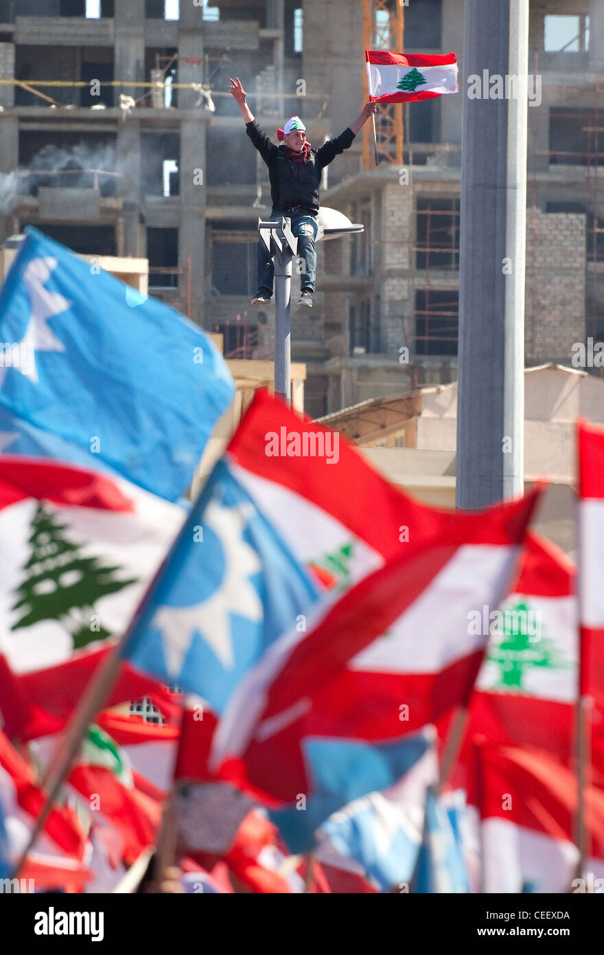 Young Lebanese man atop streetlamp waves flag high as mass political rally in Martyrs Square, Beirut, Lebanon. Flags Stock Photo