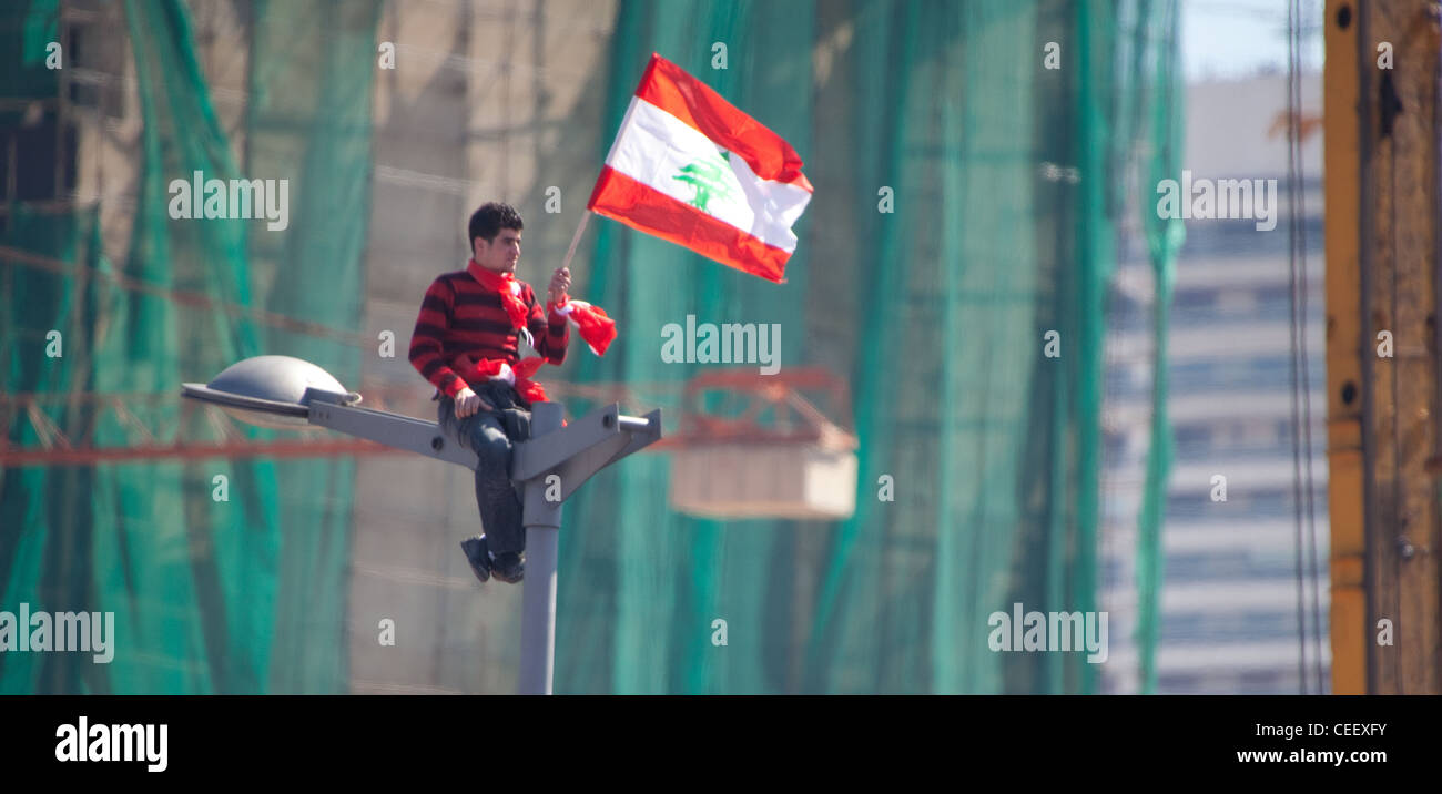 Young Lebanese man atop streetlamp waves flag high as mass political rally in Martyrs Square, Beirut, Lebanon. Stock Photo