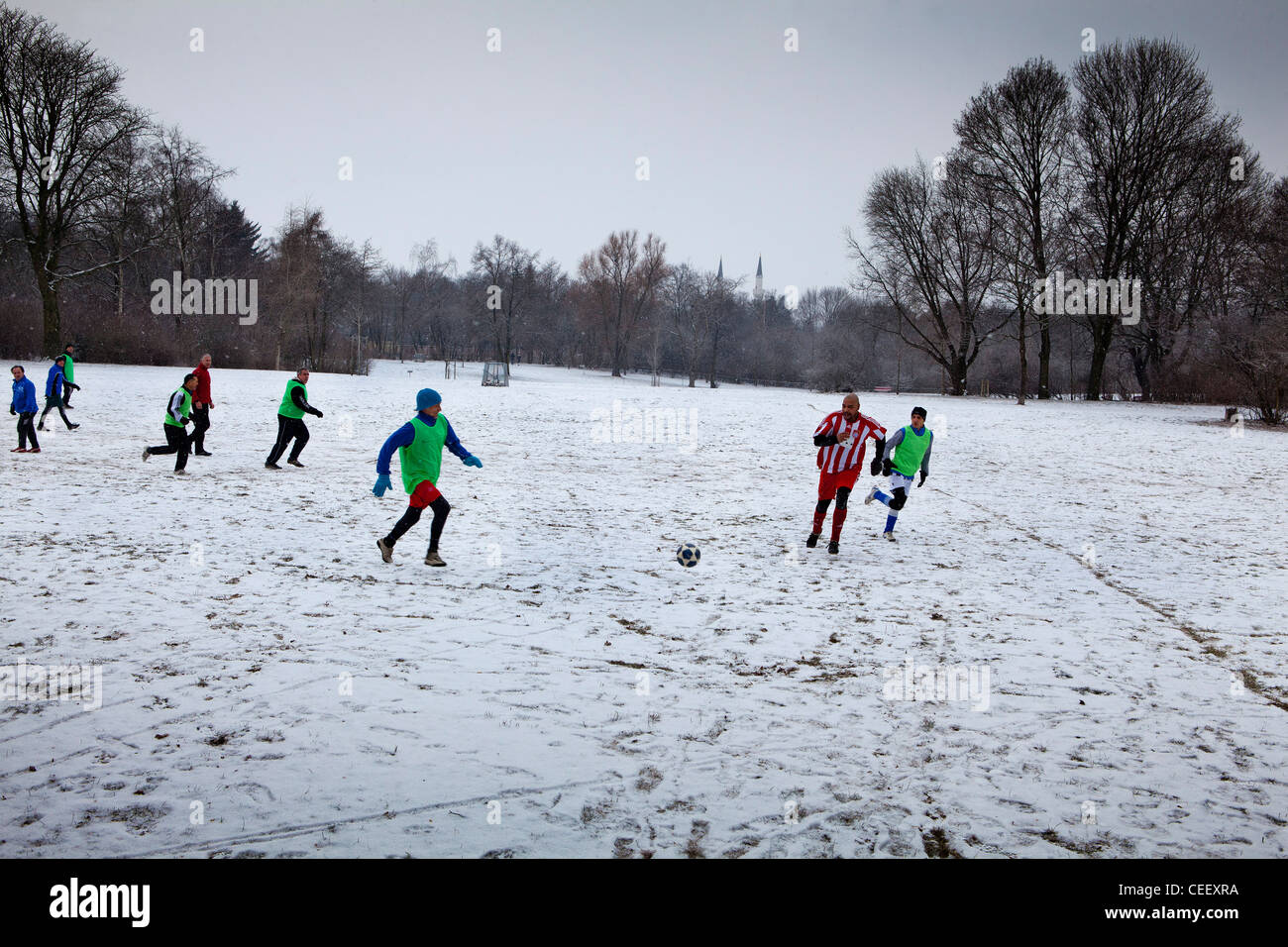 Playing winter football in the snow in the Hasenheide Volkspark, Berlin - Stock Image