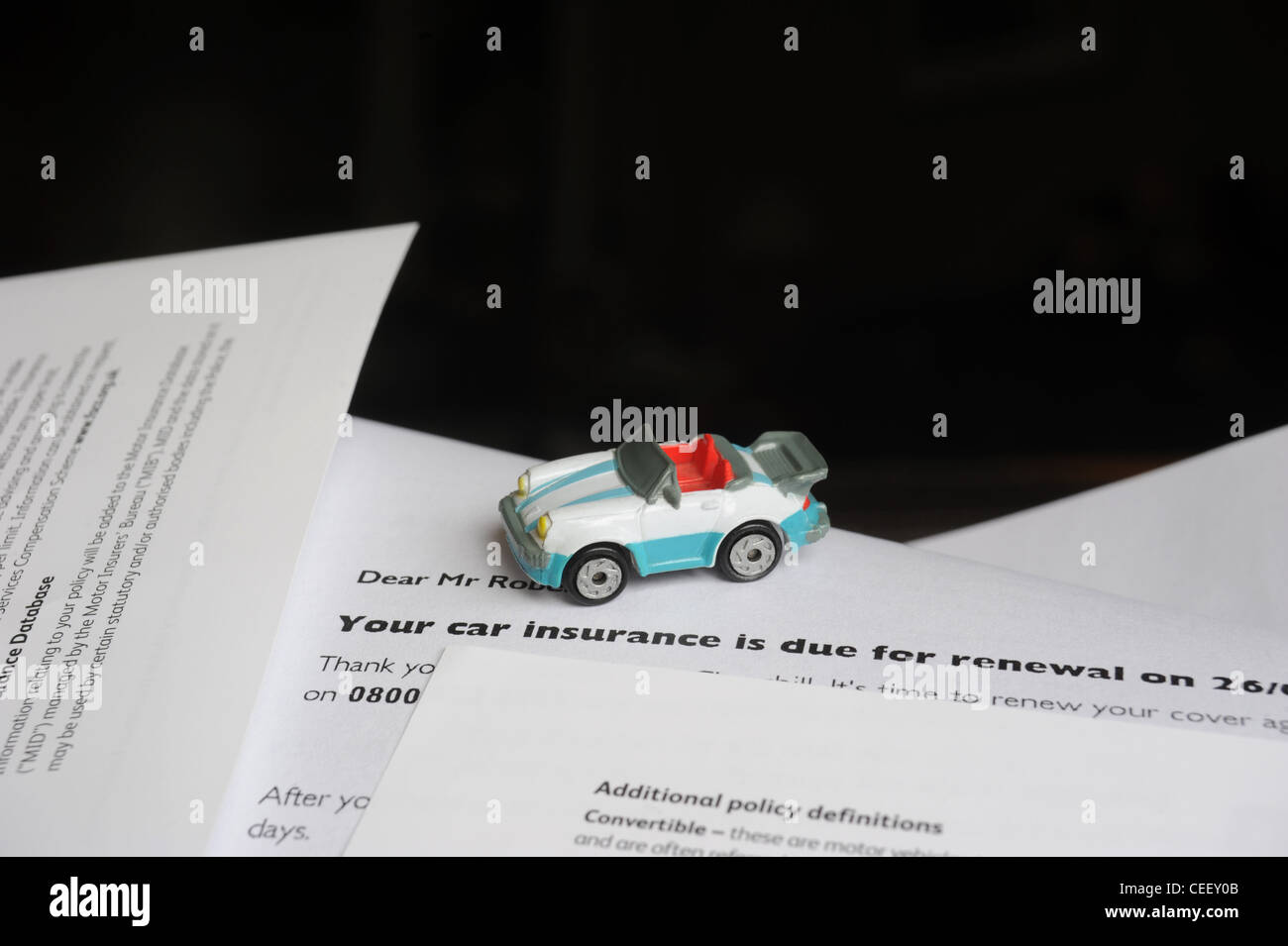 MODEL CAR WITH MOTOR INSURANCE RENEWAL LETTER RE MOTORING INSURANCE COSTS REPAIRS ACCIDENTS RUNNING HOUSEHOLD BILLS - Stock Image
