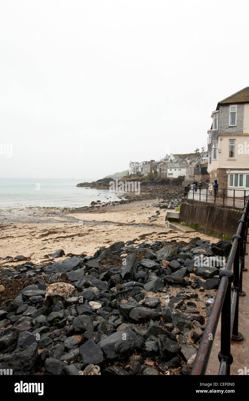 St Ives, Cornwall, England rugged coast, coastline on a dull day sand and seaweed washed up on shore - Stock Image