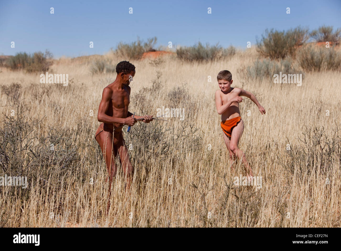 White boy and a bushman in Kagalagadi Transfrontier Park, Xaus camp, Namibia Africa - Stock Image
