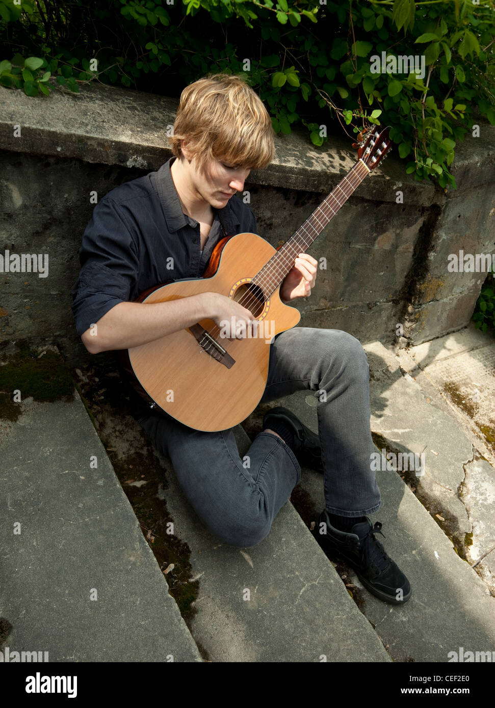 Young man sitting on old cement stairway, playing a classical guitar. - Stock Image
